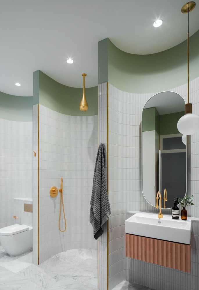 Parede verde menta no banheiro valorizada pelos detalhes em rosa e dourado
