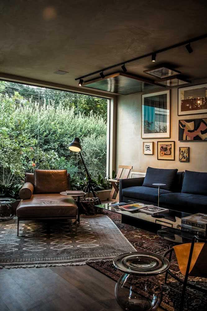 Sofá divã de couro na sala de estar. O móvel combina com a proposta sóbria e sofisticada do ambiente
