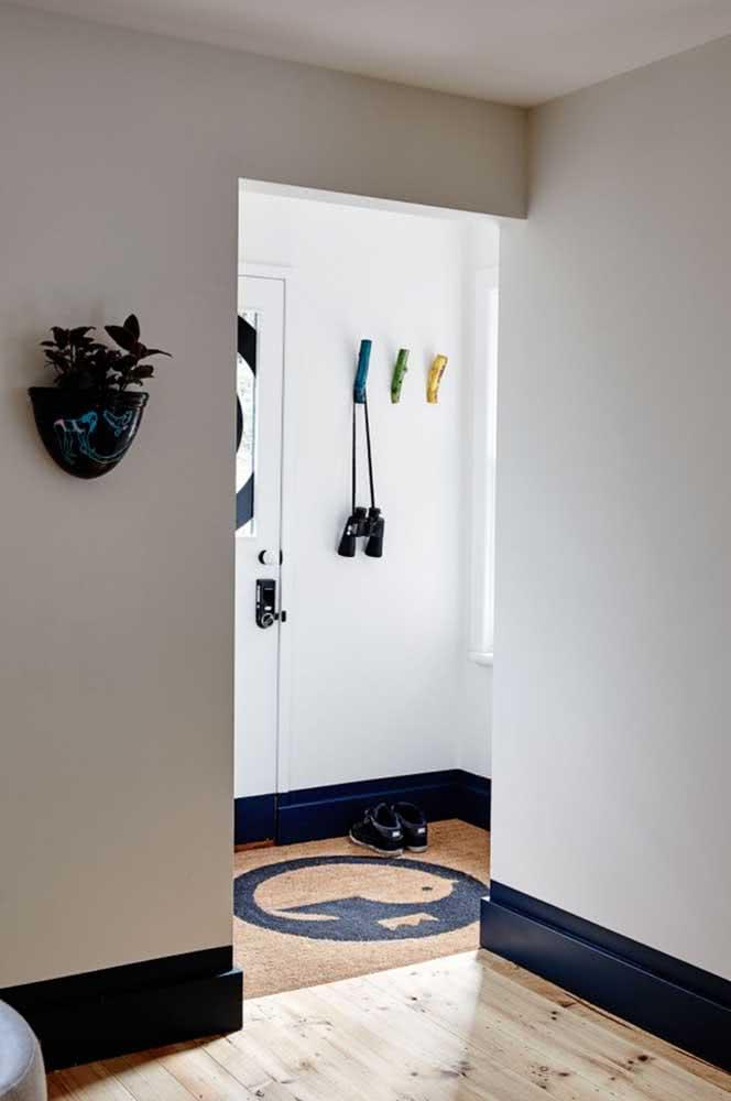 Aqui, o hall de entrada pequeno se resume aos ganchinhos na parede