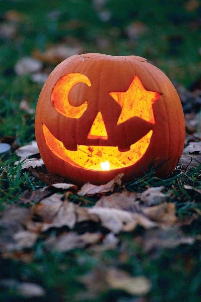 Abóbora de halloween com luz. Repare no desenho criativo de lua e estrela no lugar dos olhos