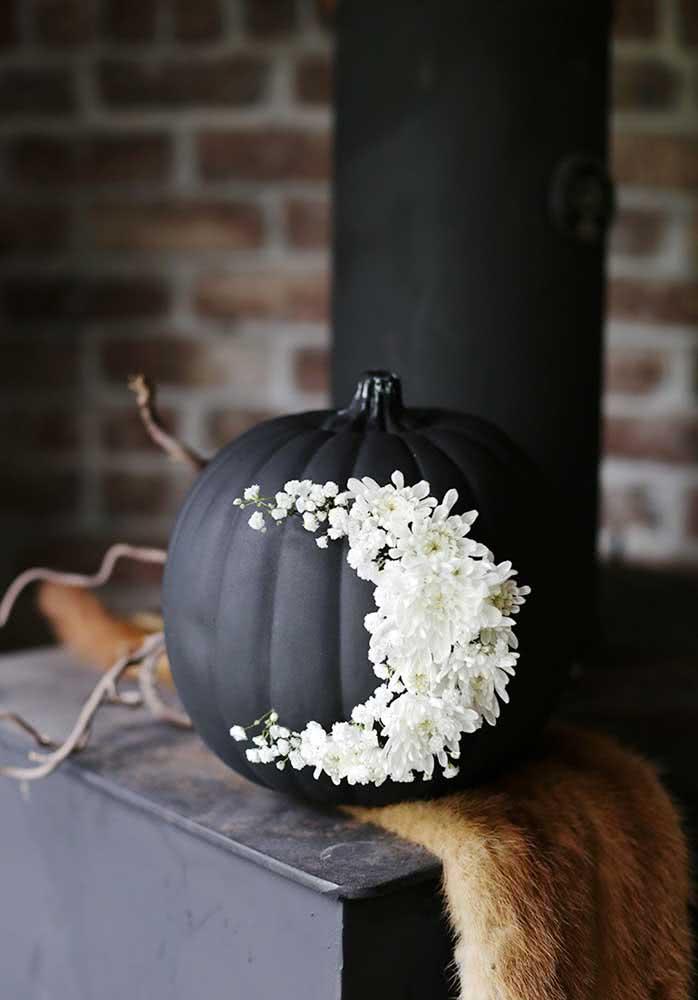 Pinte a abóbora de halloween de preto e decore com flores brancas