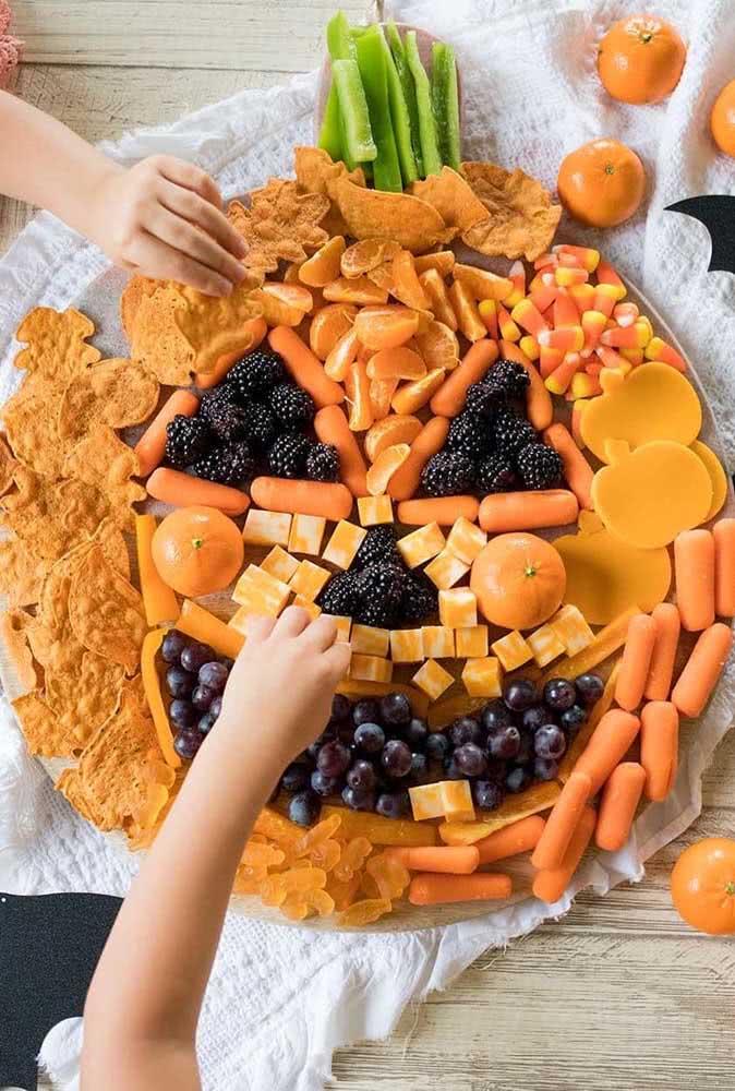E o que acha de formar um desenho de abóbora de halloween na tábua de aperitivos?