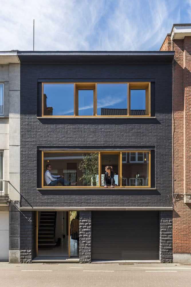Que tal uma fachada de casa moderna toda preta? O charme a mais fica por conta dos tijolinhos