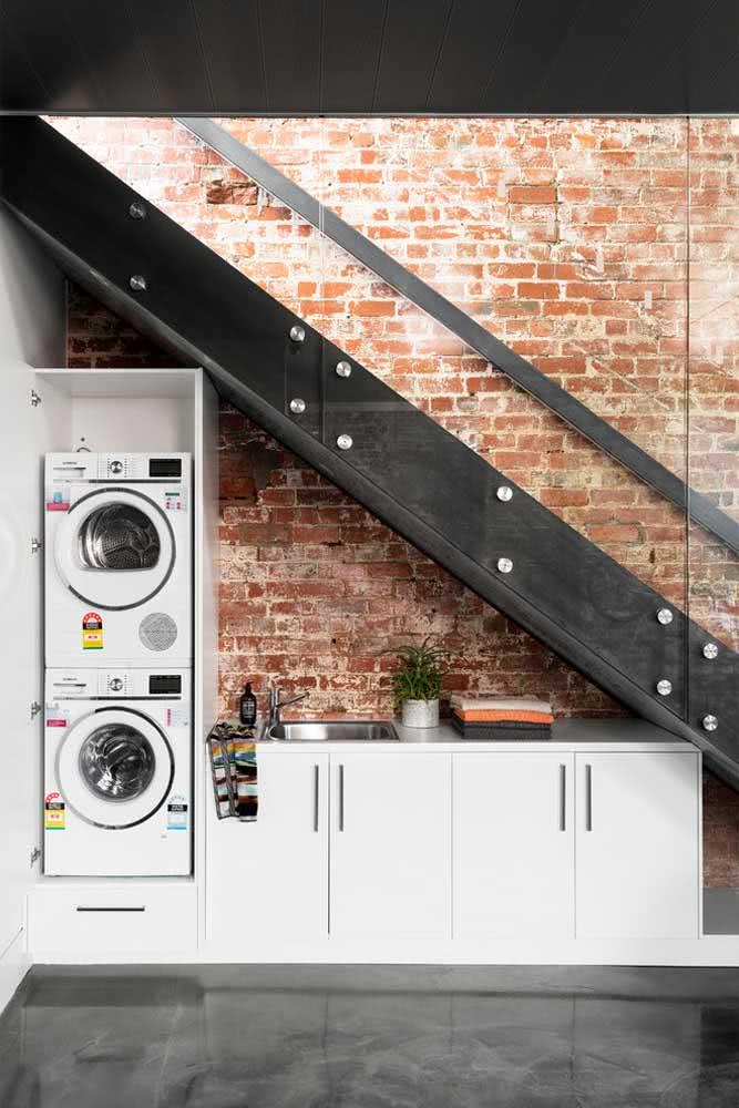Espaço inusitado embaixo da escada: área de lavanderia com pia e máquinas de lava e seca.