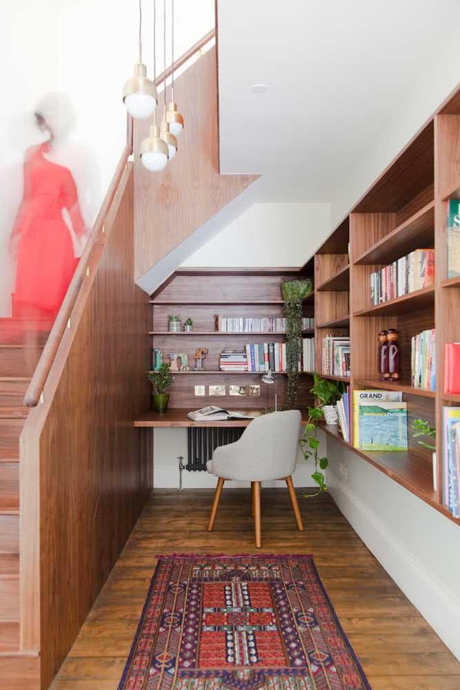 Home office amplo e com prateleiras ao redor da escada.