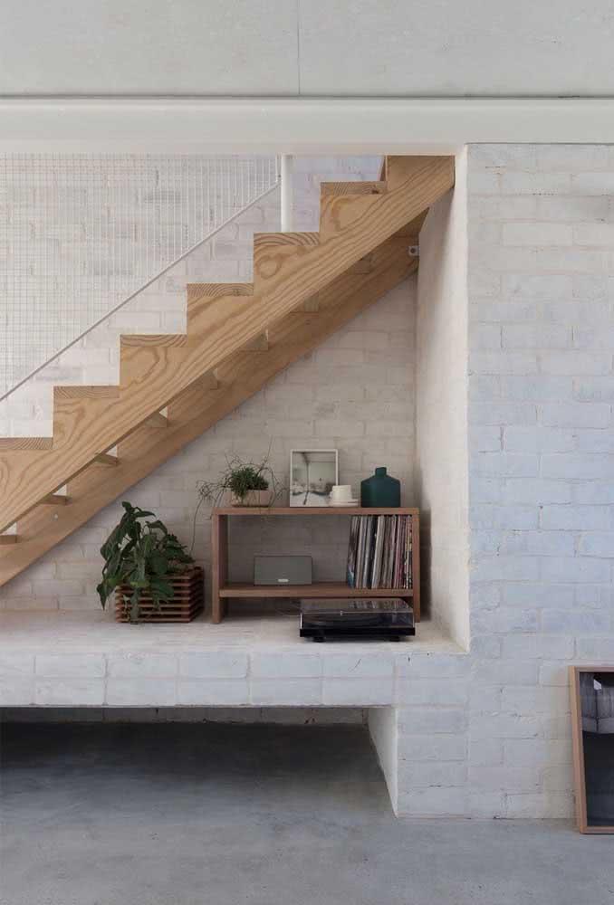 Cantinho da música com vitrola e discos de vinil dispostos embaixo desta escada.