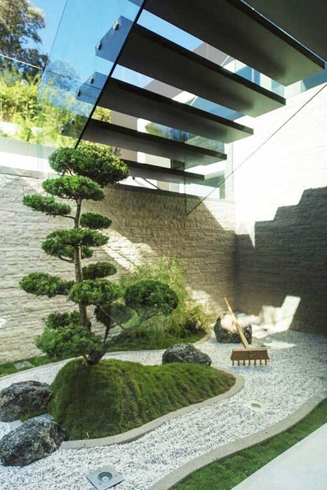 Jardim japonês com árvore de bonsai embaixo de uma escada.