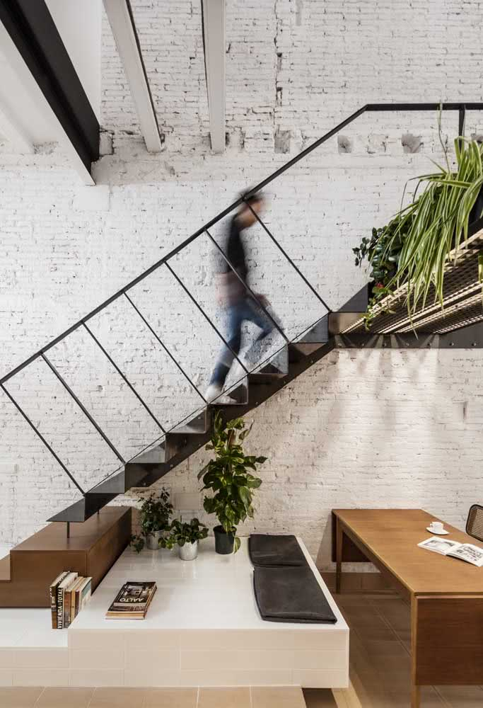 Prateleira para livros, espaço para vasos e mesa embaixo da escada.