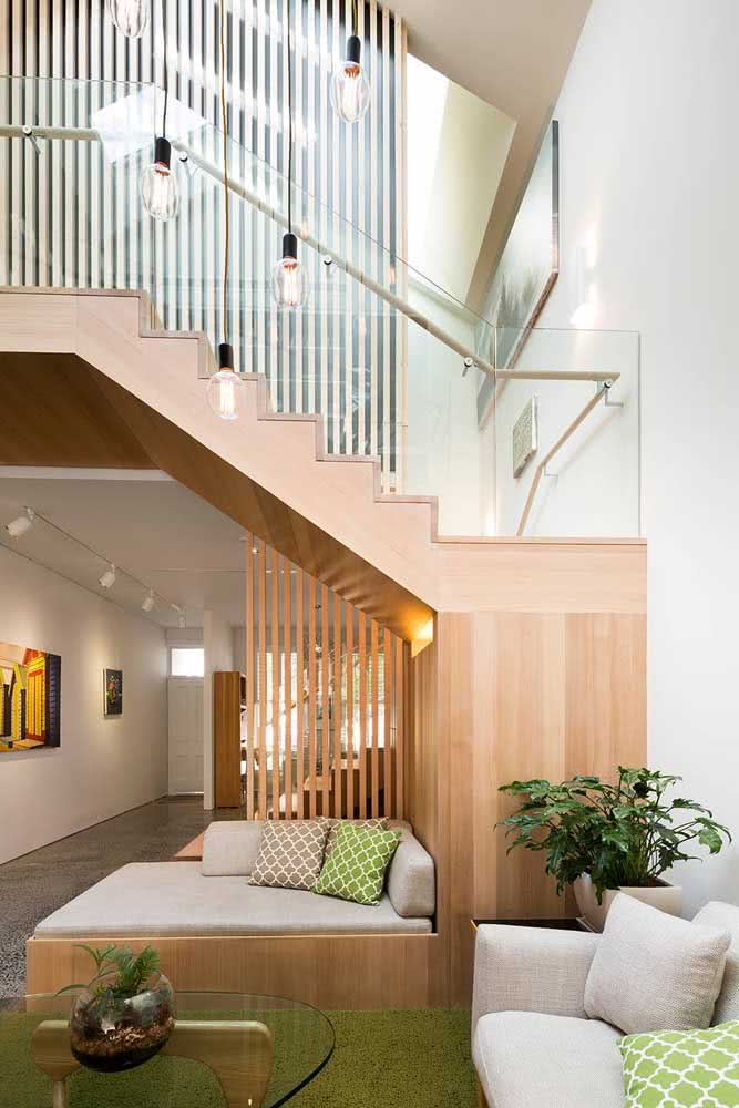 O espaço embaixo da escada foi utilizado para abrigar o sofá e complementar a sala de estar.
