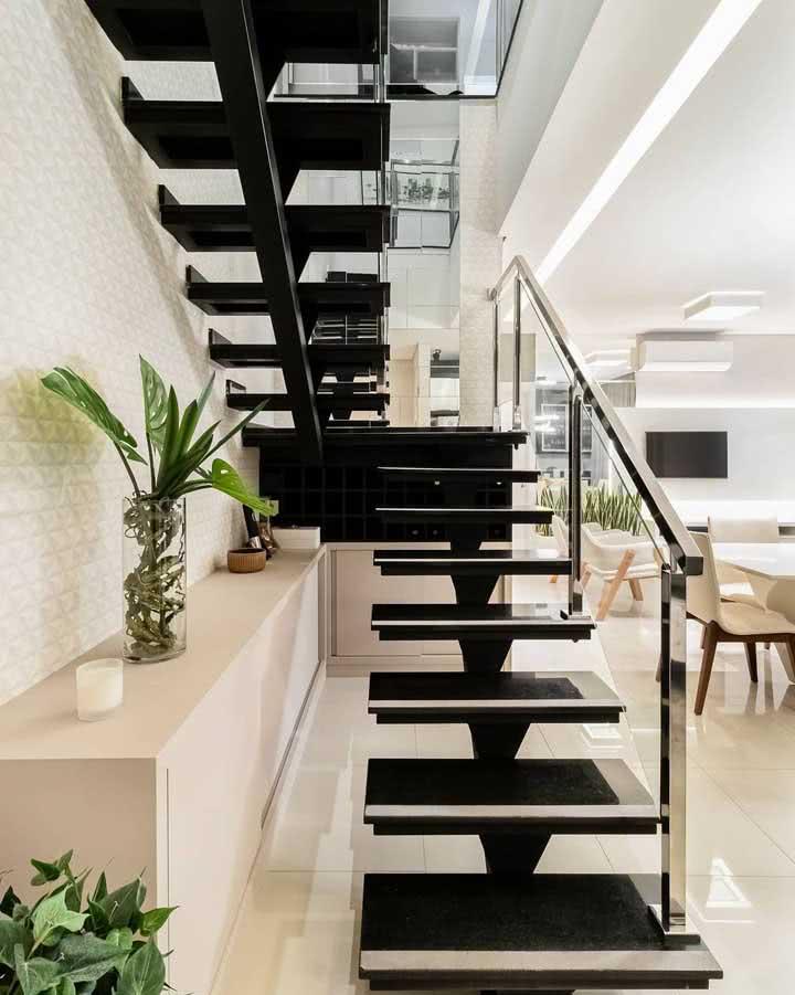 Mesmo um espaço de escada em U não deve ser ignorado: aqui um móvel do tipo buffet complementa a sala de jantar da residência.