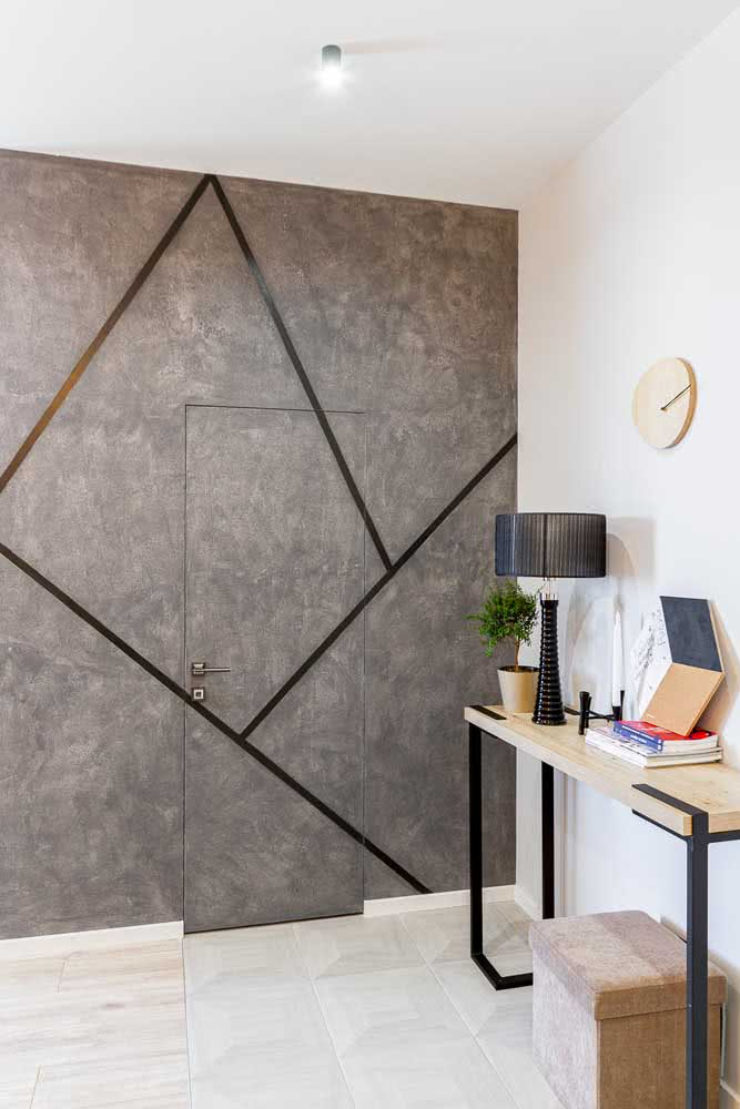 Pintura geométrica na parede feita com tinta cinza e fita adesiva