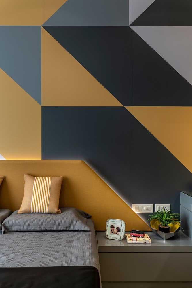 Aqui, a cabeceira da cama acompanha a cor usada na pintura geométrica da parede
