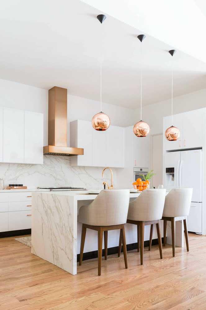 A cozinha clássica e elegante apostou nos pendentes cobres para trazer um pouco de modernidade à decoração