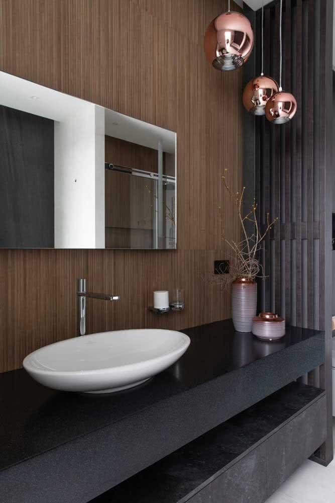 Pendente cobre no banheiro formando uma linda composição com o painel amadeirado e os detalhes em cinza
