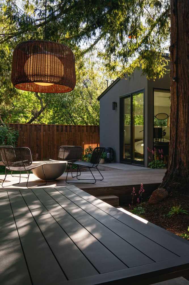 O deck de madeira e a iluminação são o destaque da decoração desse quintal pequeno