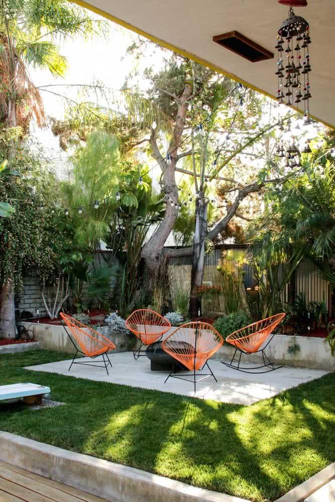 As cadeiras laranjas são o ponto focal desse quintal pequeno com jardim