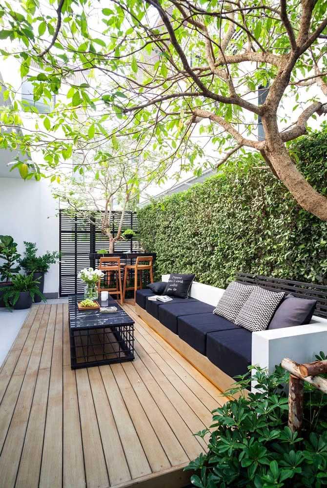 Quintal pequeno planejado com sofá e deck de madeira. Conforto e tranquilidade!