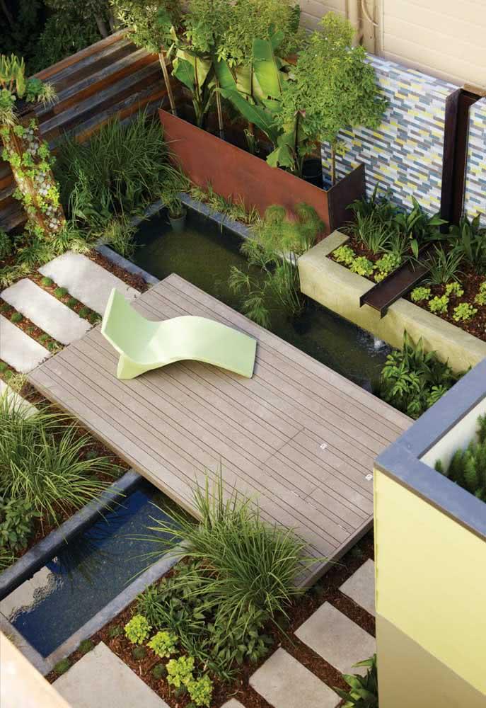 Um mini lago no quintal pequeno com deck de madeira e espreguiçadeira. O local perfeito para uma tarde relaxante