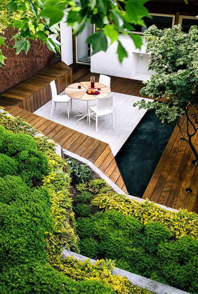 Ideia para quintal pequeno: faça um jardim vertical e use deck de madeira no piso