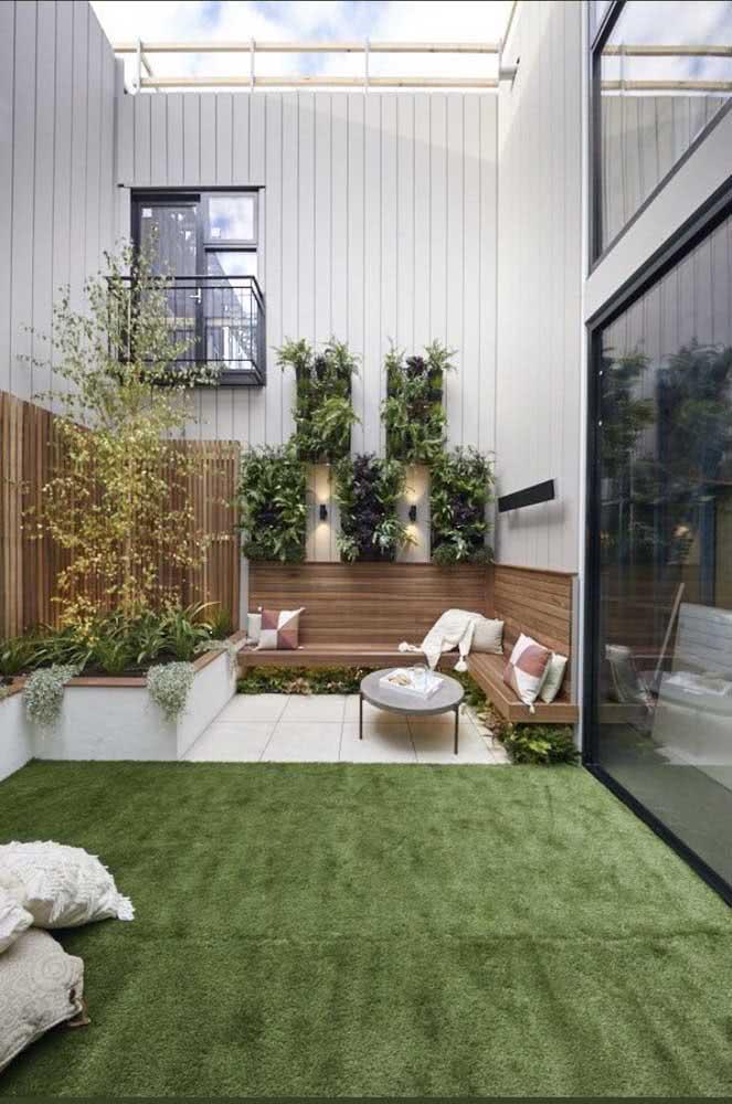 Quintal pequeno decorado com móveis de madeira e grama sintética