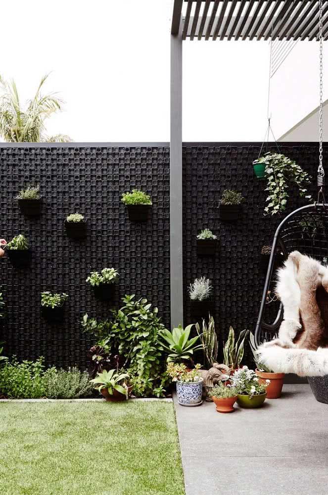 Aqui, o jardim vertical ajuda a economizar espaço na decoração do quintal pequeno