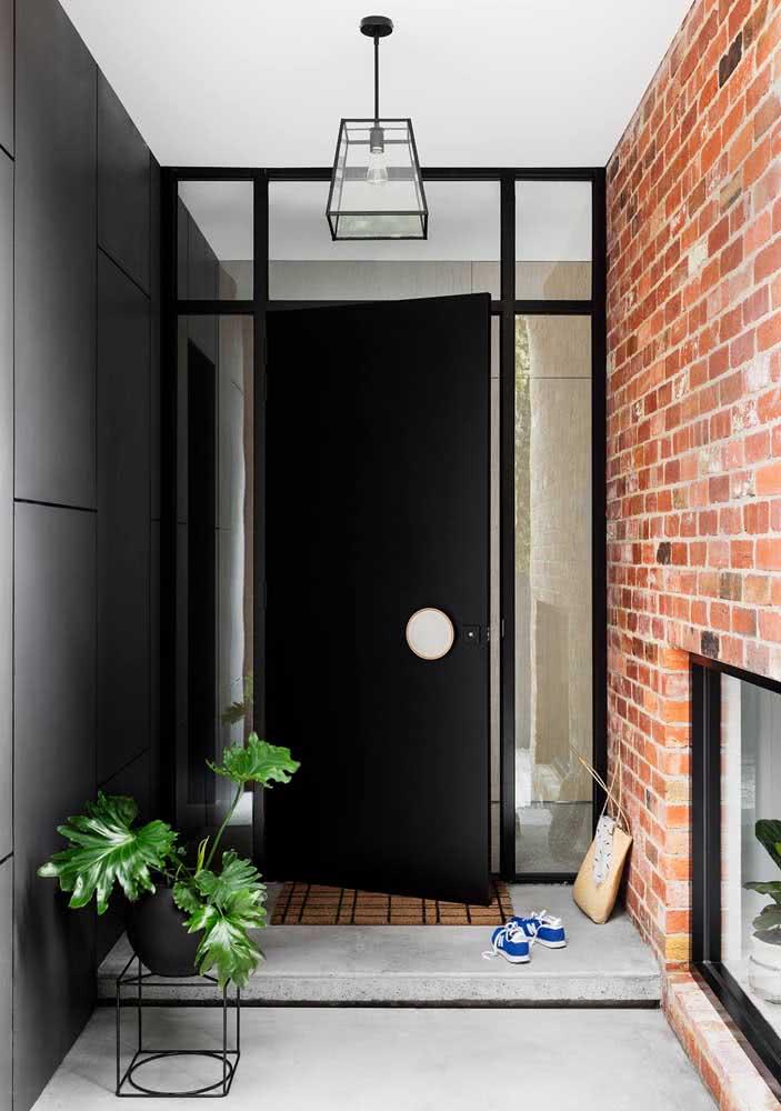Porta pivotante preta para entrada da casa. Destaque para a moldura de vidro