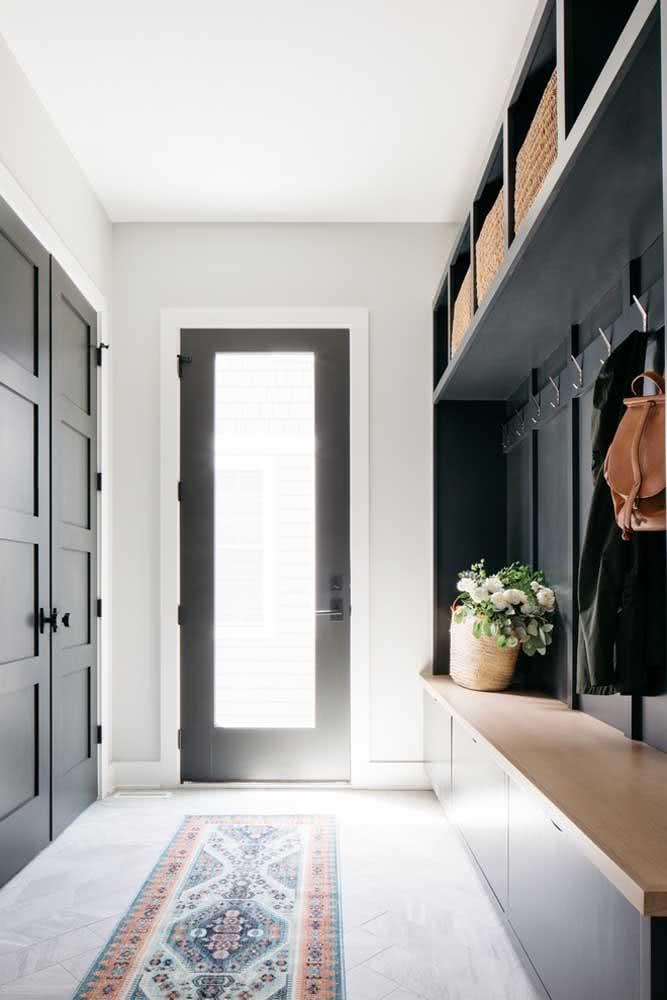 Porta de vidro preta combinando com a decoração do hall de entrada