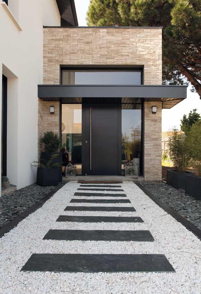 Porta de madeira preta valorizando a fachada de elementos naturais