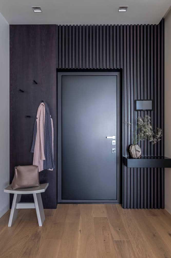 Aqui, o destaque fica para o painel de madeira que emoldura a porta preta simples