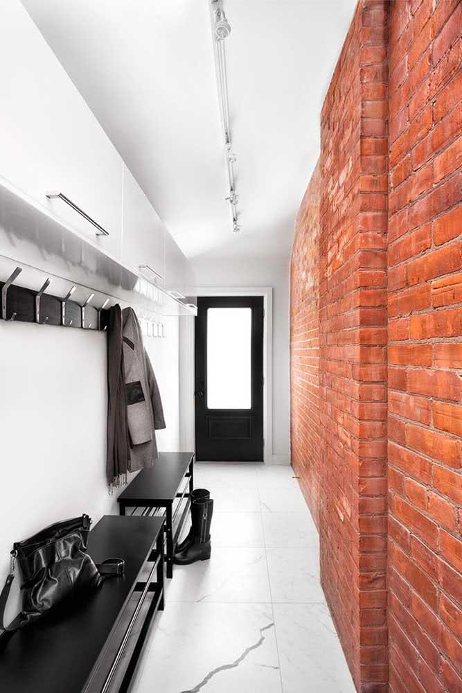 A parede de tijolinhos forma um lindo contraste com a porta preta