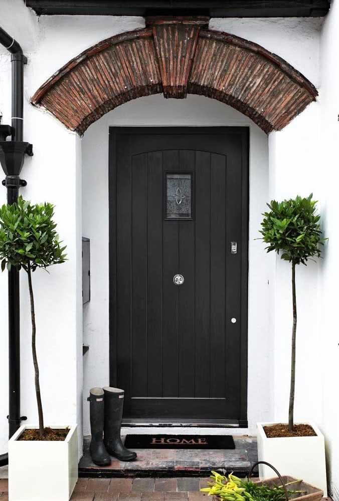 Uma porta preta clássica e aconchegante na entrada da casa