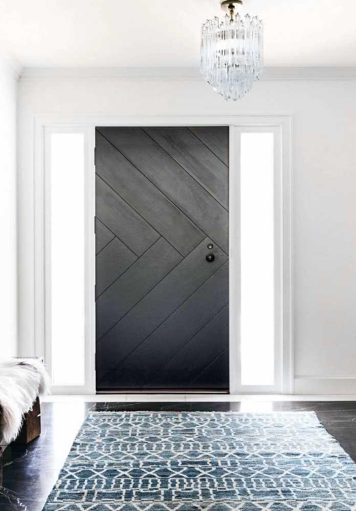 Porta de madeira preta contracenando com a parede branca da sala