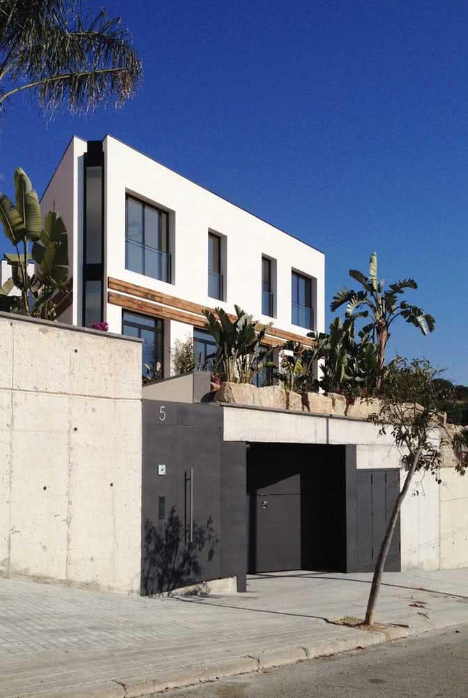 Porta e muro pretos para criar unidade visual na fachada moderna da casa