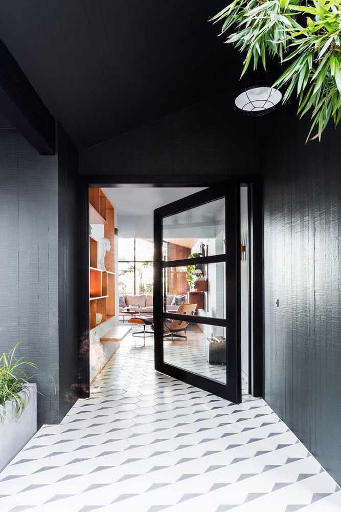 Aqui, a porta pivotante preta revela uma casa moderna e de personalidade