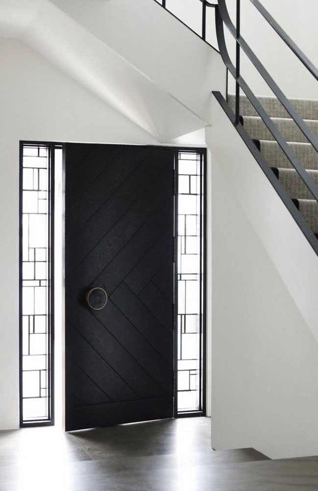 Porta de entrada preta. Aqui, o puxador diferenciado completa o visual sofisticado da porta