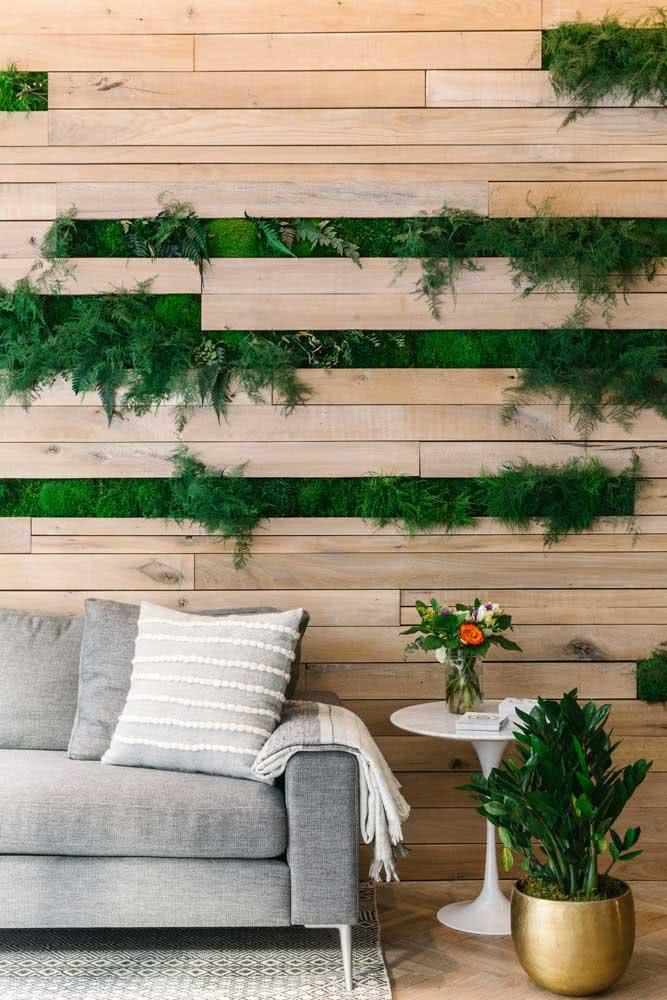 Que tal uma ideia diferenciada para o jardim vertical artificial interno? Aqui, ele foi montado entre as tábuas do painel de madeira