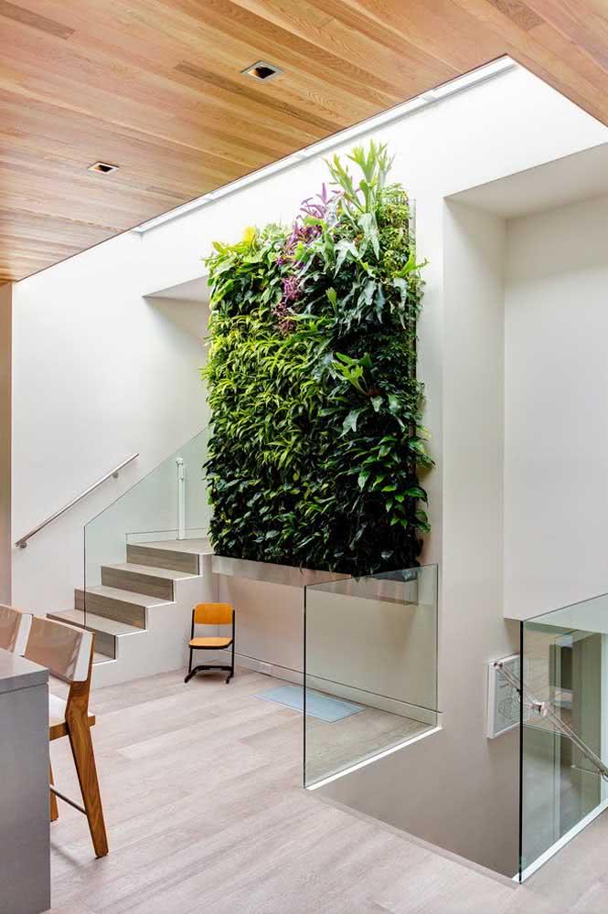 As paredes brancas realçam o verde das plantas do jardim vertical artificial interno