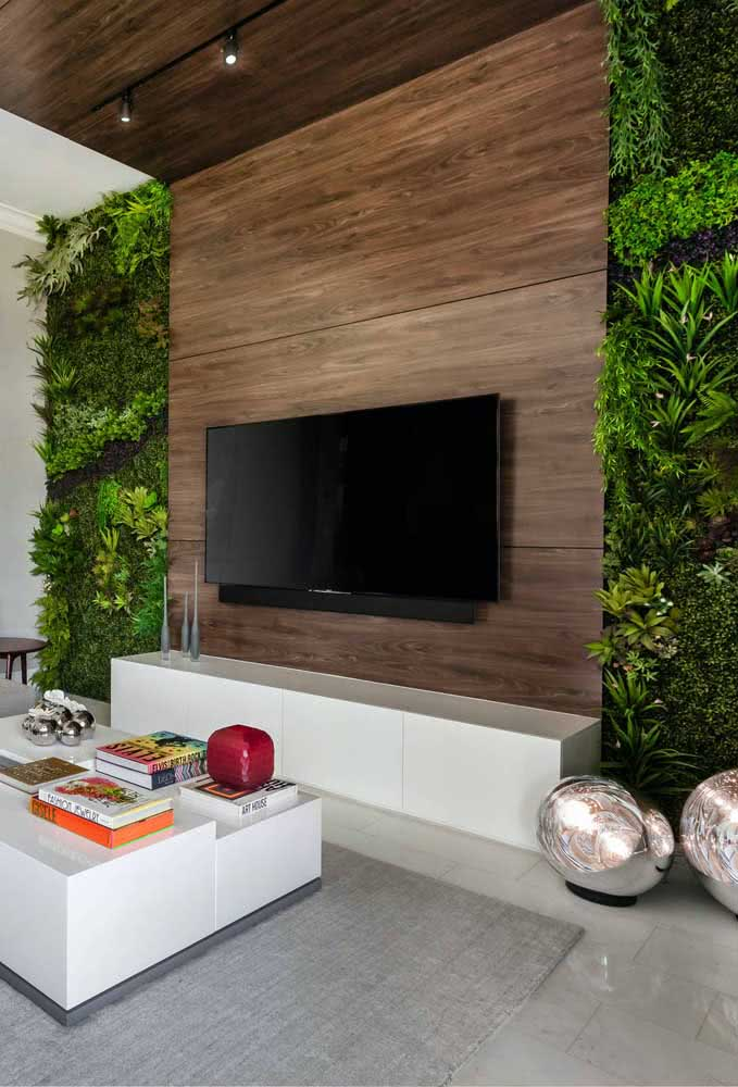 Jardim vertical artificial para sala formando uma moldura verde ao lado da televisão