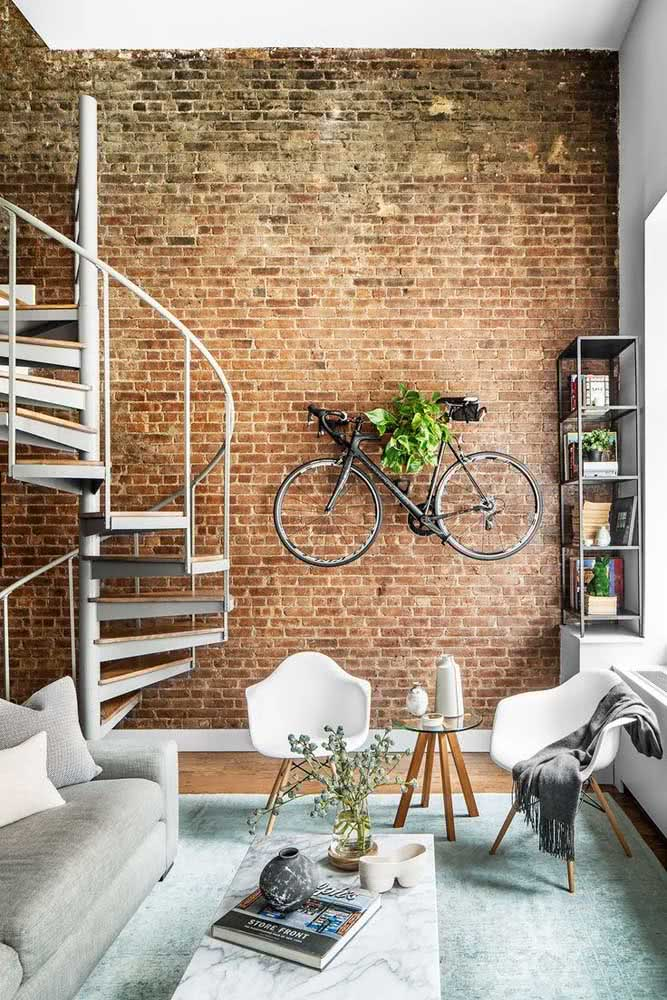 Um típico loft industrial com paredes de tijolinho, pé direito alto e cores neutras