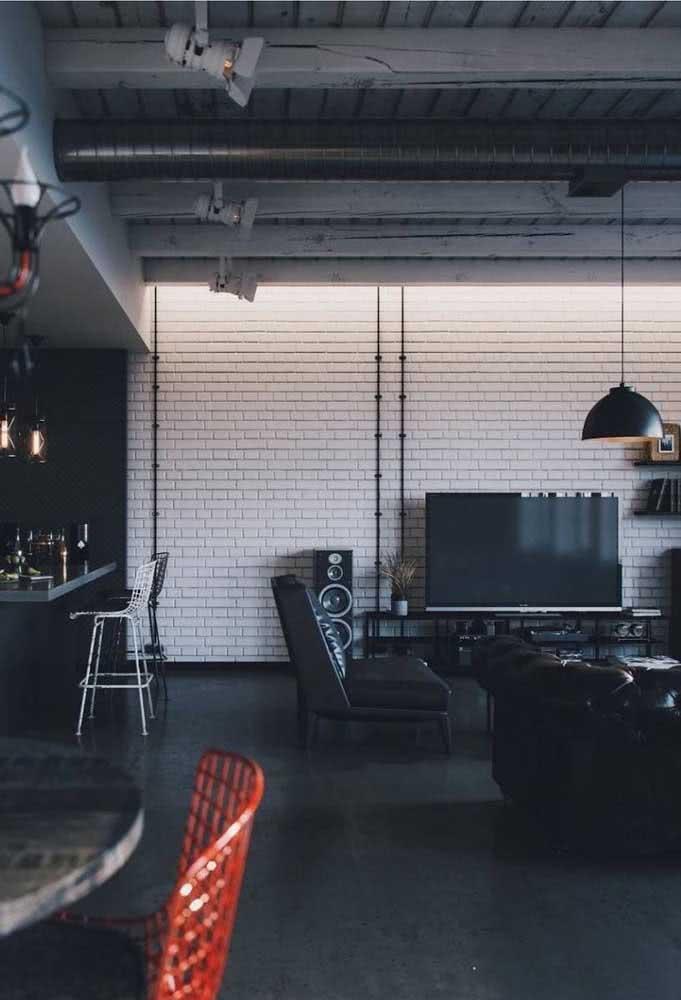 Loft industrial com paredes de tijolinho branco para ajudar na iluminação