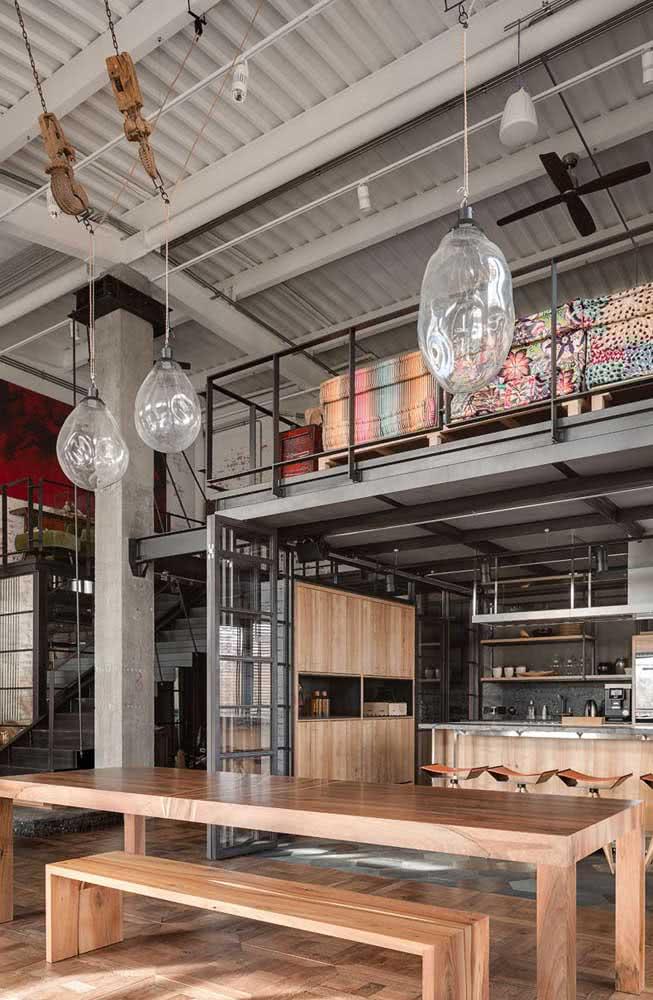 Luminárias pendentes chamam a atenção para o pé direito alto do loft industrial