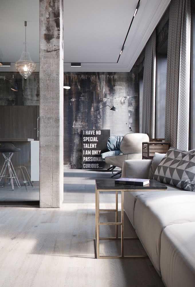O lustre de cristal e os elementos dourados trazem um toque de glamour ao loft industrial