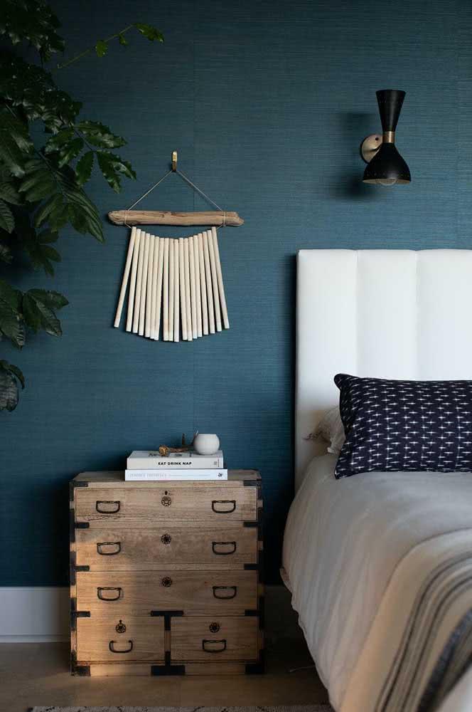 Quarto de casal com estilo praiano tem cômoda de madeira e papel de parede azul.