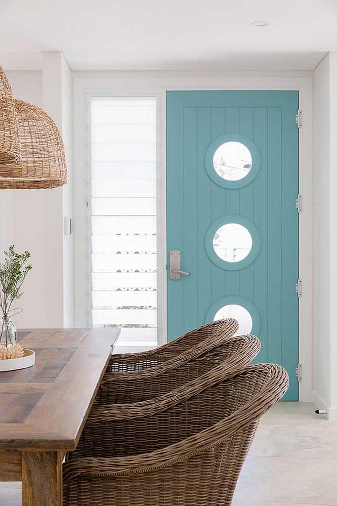 Porta de entrada pintada na cor azul petróleo. Os itens em palha e madeira tem a cara do estilo praiano.