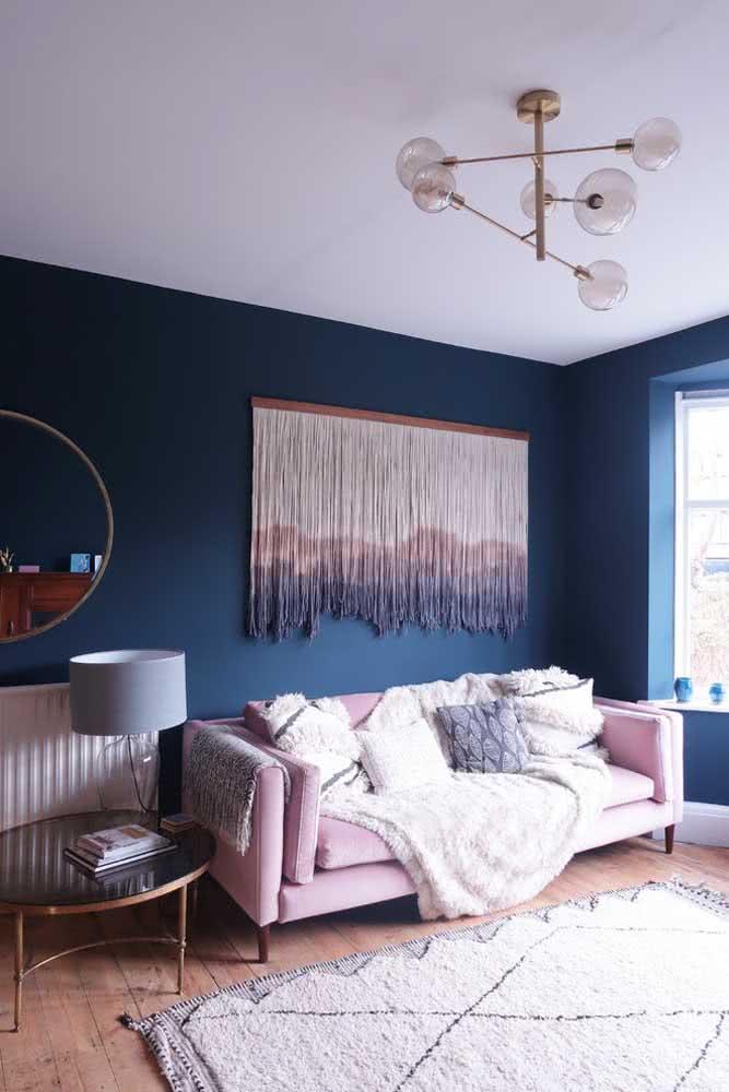 Sala de estar com pintura azul marinho na parede e sofá rosa