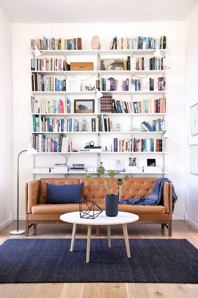 Sofá de couro em uma sala de estar com escrivaninha e tapete azul marinho. A manta e a capa de almofada acompanham a mesma tonalidade.