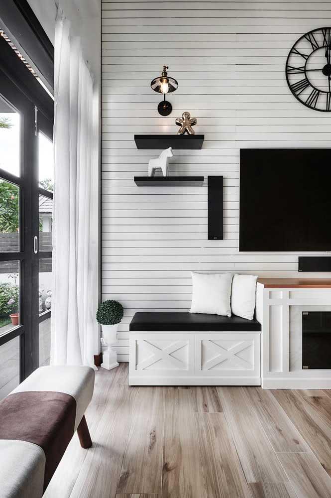 Sala de TV com parede de madeira que remete as construções localizadas no litoral.
