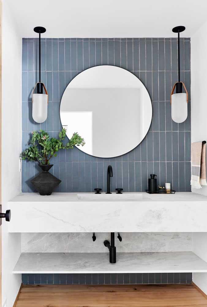 Além dos metais na cor preta, este banheiro tem o revestimento da parede na cor azul.
