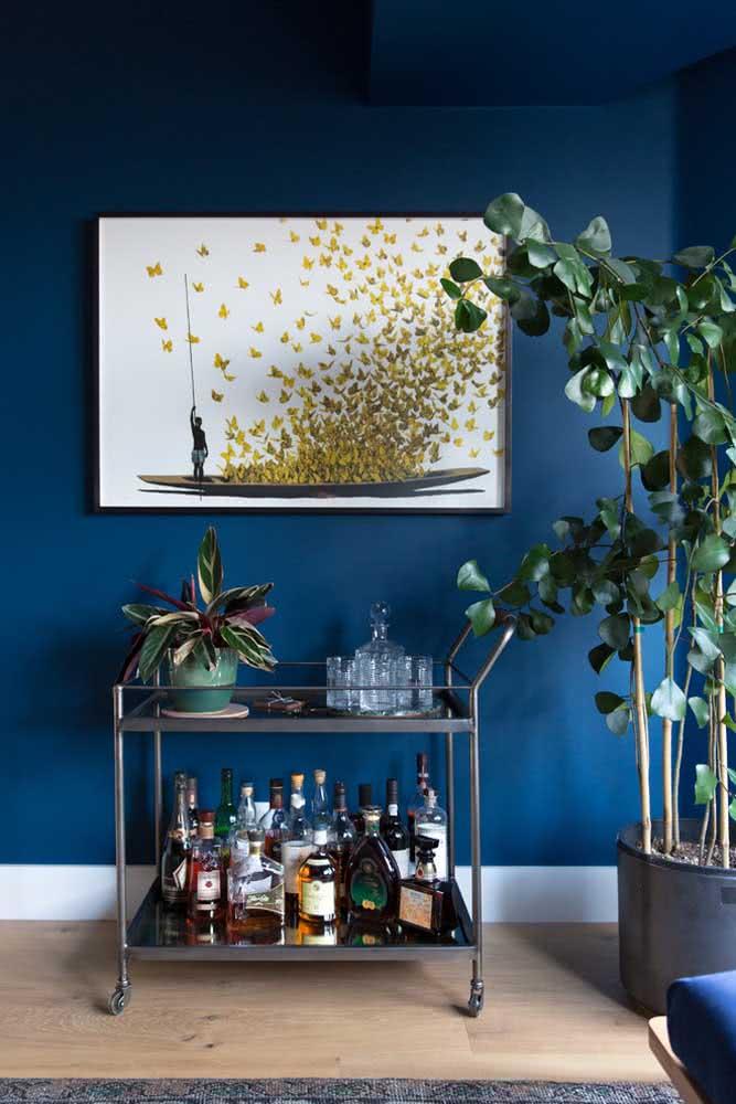 Cantinho do bar com parede pintada na cor azul marinho. Detalhe para o quadro com ilustração de barco em rio com pássaros amarelos.