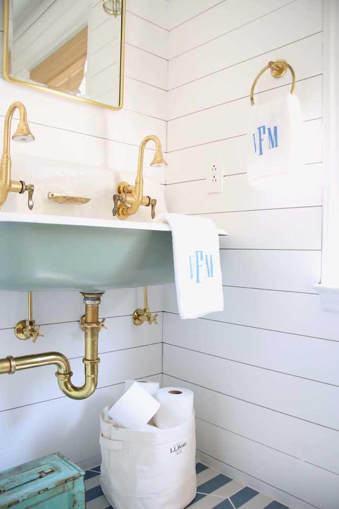 Banheiro com parede de madeira branca e metais dourados.
